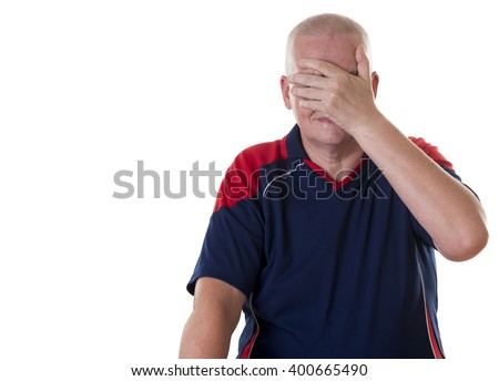 Embarrassed elderly man with shaved head covers his face with hand against a white background