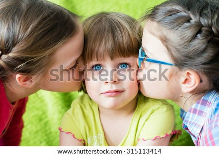 Embarrassed girl looking at camera. Toddler girl being kissed by two sisters.