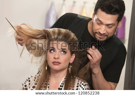 Embarrassed male hair stylist and female customer in salon - stock photo