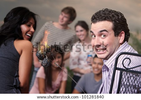 Embarrassed man with burning marshmallows at a cookout