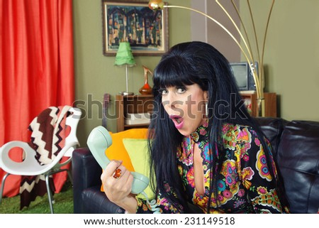 Embarrassed single 1960s woman on sofa holding telephone