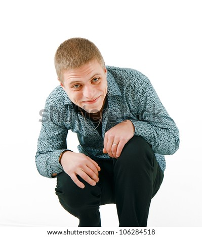embarrassed smiling man on a white background squatting - stock photo
