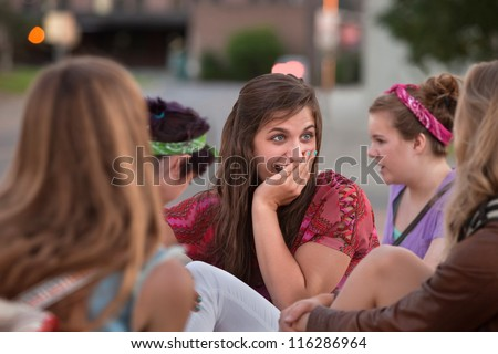 Embarrassed teenage girl with hand on mouth among friends