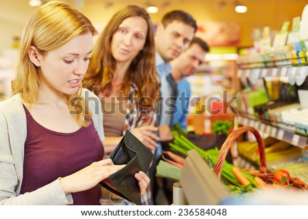 Embarrassed woman looking for money in her wallet at supermarket checkout - stock photo