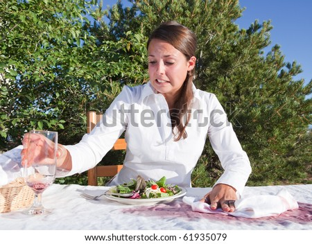 Embarrassed young woman trying to clean after spilling wine on white table cloth - stock photo