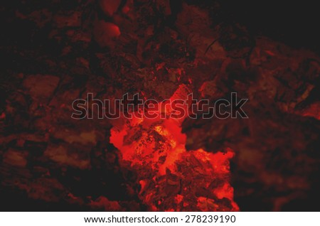 Embers are burning in a fireplace. Infernal background - stock photo