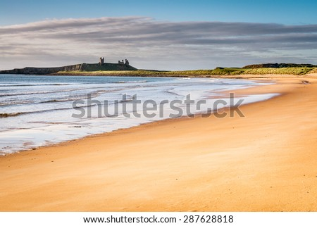 Embleton Sands / The majestic ruins of Dunstanburgh Castle provide the dramatic backdrop to the beautiful Embleton Bay - stock photo