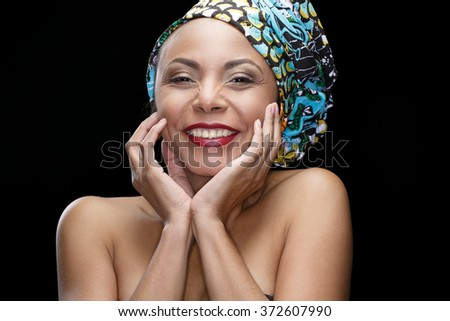 Embodying joy. Closeup portrait of a cheerful African woman wearing national ethnic headpiece laughing happily cupping her face - stock photo