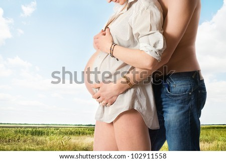 Embrace by man of belly of pregnant woman on nature background - stock photo