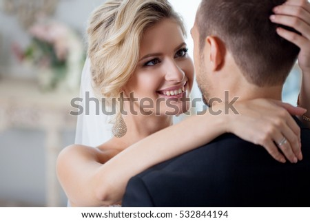 Embrace on wedding day. Beautiful bride embracing groom in the neck