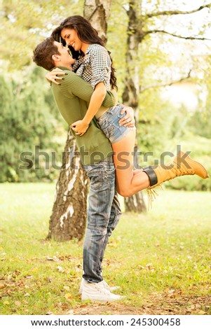 Embrace the young loving couple in the park. The guy rising hot girlfriend in height in a passionate embrace. - stock photo