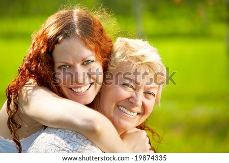 Embraces happy mothers with the adult daughter against a lawn - stock photo