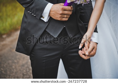Embraces of hands of the newly-married couple.