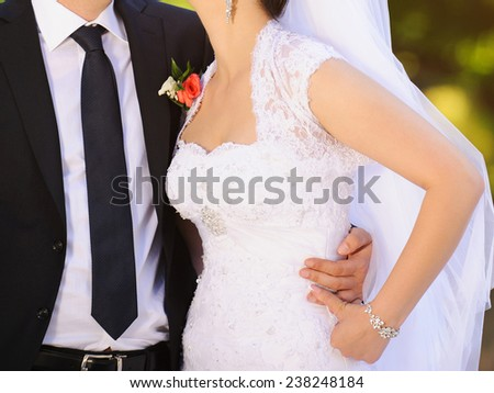 embracing bride and groom in park - stock photo