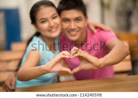 Embracing couple producing a well-known gesture of love, a hand-made heart shape - stock photo