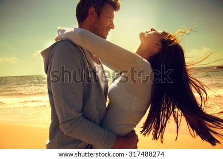 embracing dancing carefree couple on beach - stock photo