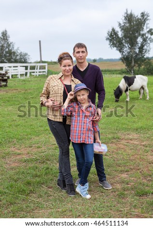 Embracing family of three people standing together on backyard of countryside farm