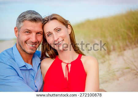 embracing love couple on the coast  - stock photo