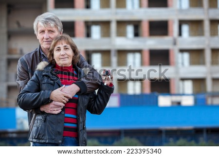 Embracing loving senior couple with house key in hand, copyspace - stock photo