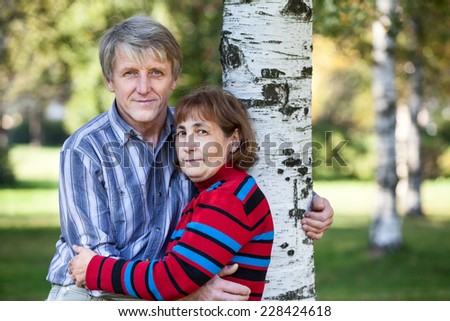 Embracing mature husband and wife standing next to tree in park - stock photo
