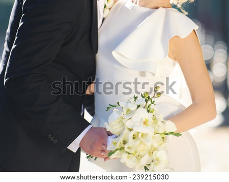 embracing newlyweds with orchid bouquet in street - stock photo
