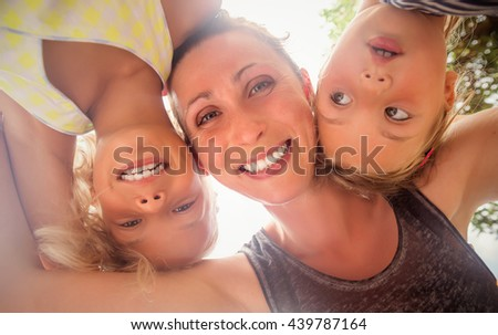 embracing selfie of mother with daughters - stock photo