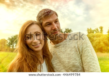 embracing walking younger couple through landscape - stock photo