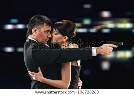 embracing woman and man on night background, man holds a pistol