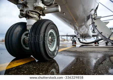 Embraer ERJ 145 aircraft landing gear on the runway - stock photo