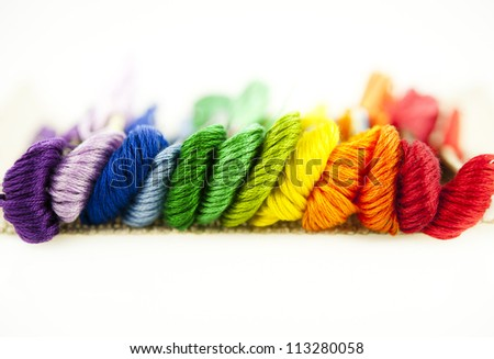 Embroidery threads of every color of the rainbow on a white background