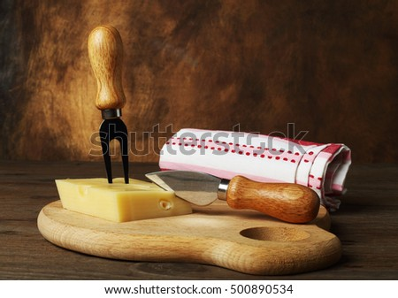 Emental cheese and a knife on a wooden board