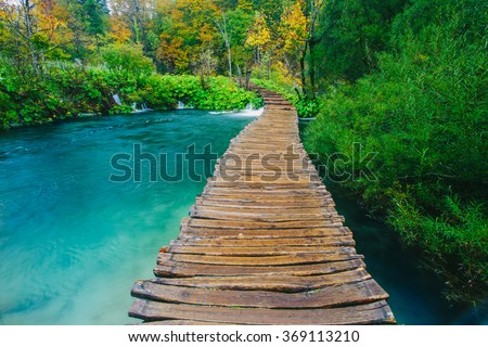 Emerald colored stream with crystal clear water with wooden pathway. Plitvice lakes, Croatia - stock photo