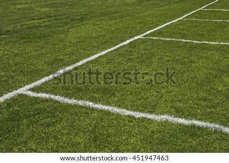 Emerald grass of a playing field with painted white lines.