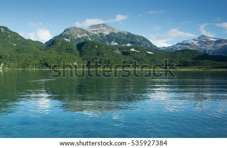 emerald green forest covered mountains of alaska reflecting in a calm bay with blue skies