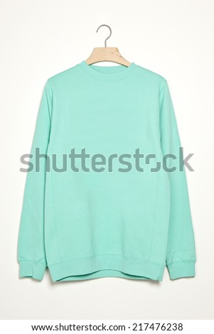 emerald green long shirts with wood hanger isolated white. - stock photo