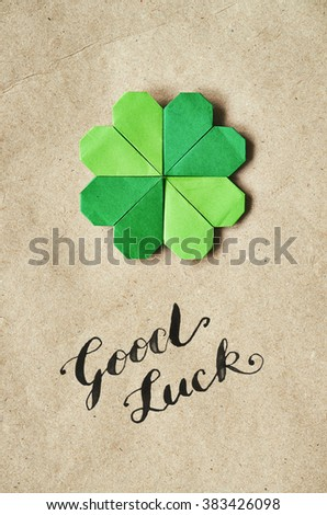 Emerald green paper folded origami clover shamrock leaf on craft paper eco background. Good Luck brush nib lettering calligraphy Patrick's Day postcard. - stock photo