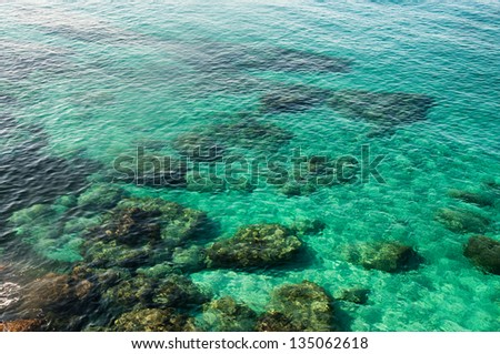 Emerald green sea water with rock  on Cyprus - stock photo