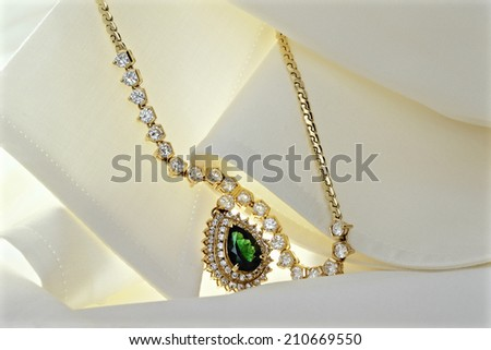 Emerald Pendant Decorated With Diamonds On A Silk Blouse - stock photo