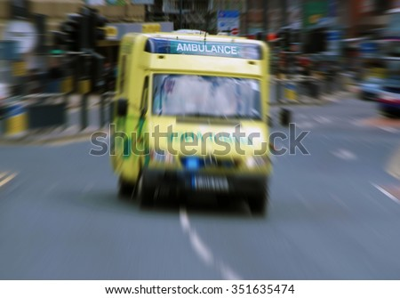 Emergency ambulance travels through city street. Zoom effect applied for dramatic effect. - stock photo