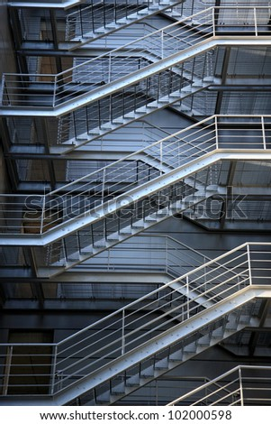 emergency evacuation metallic stairs at the back side of building - stock photo