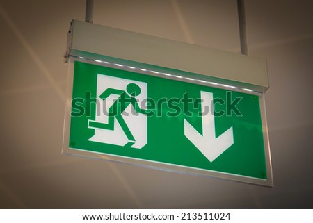 Emergency exit sign above a black doorway - stock photo
