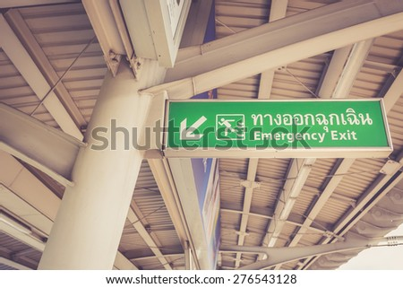 Emergency exit sign in sky train station, Bangkok, Thailand - stock photo