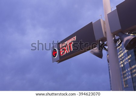Emergency exit sign. Outdoor sign. Illuminated, glowing exit sign - stock photo