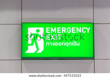 Emergency exit sign with Thai alphabet isolated on white background.