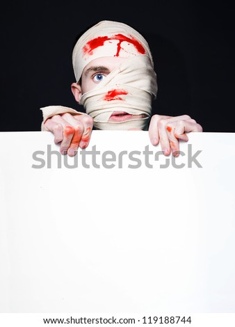 Emergency Room Casualty Covered In Blood After Car Crash Holding Insurance Advertisement Sign - stock photo