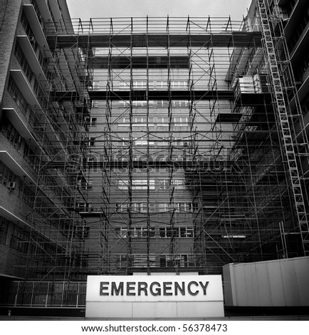 Emergency room sign at a hospital with chaotic construction work going on in black and white - stock photo