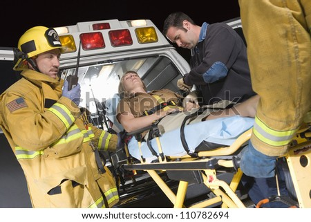 Emergency service professionals carrying patient on stretcher in ambulance - stock photo