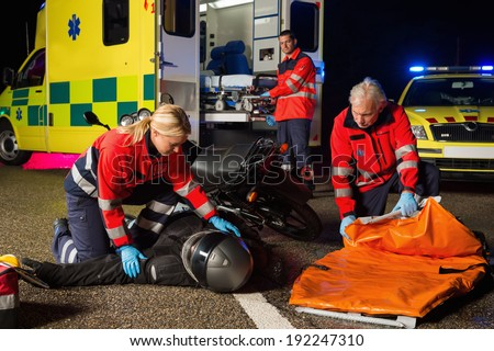 Emergency team assisting injured motorbike man driver at night - stock photo