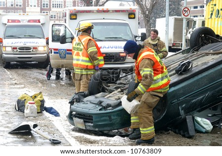 Emergency workers respond to a single vehicle rollover. - stock photo