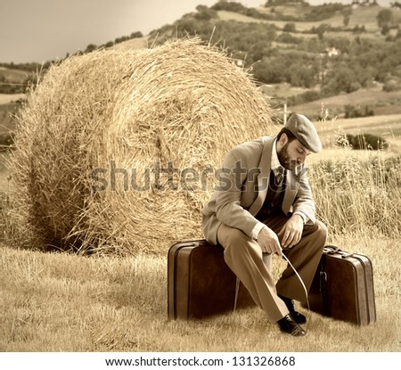 Emigrant man with the suitcases in wheat field - stock photo